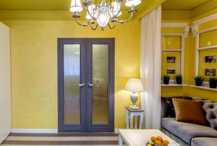 сочетание желтых стен с темно-коричневой дверью с стеклянными вставками