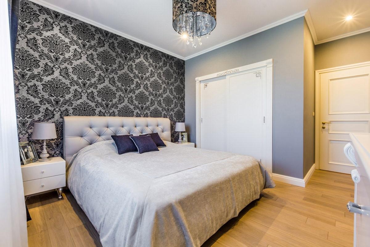 Серые обои с темным вензельным рисунком в интерьере спальни