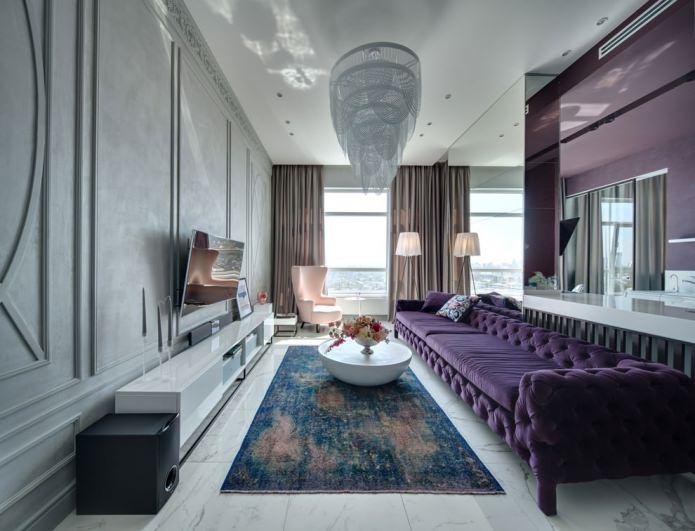 интерьер гостиной с фиолетовым диваном и красивой люстрой
