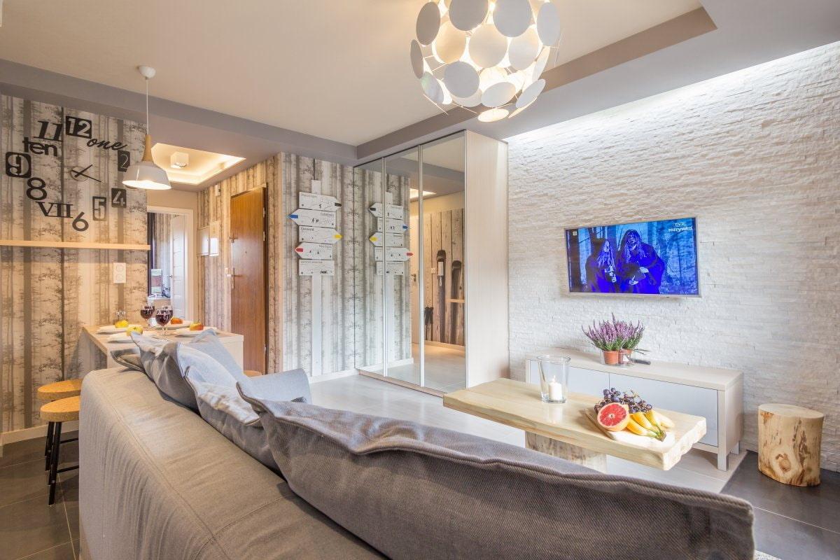 Сочетание белого камня с обоями в гостиной