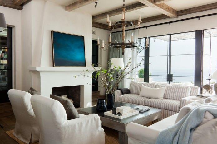 интерьер гостиной с декоративными балками и кованной подвесной люстрой