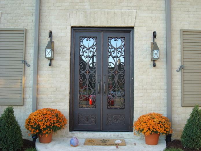 крыльцо загородного дома с входной дверью с ковкой и стеклом