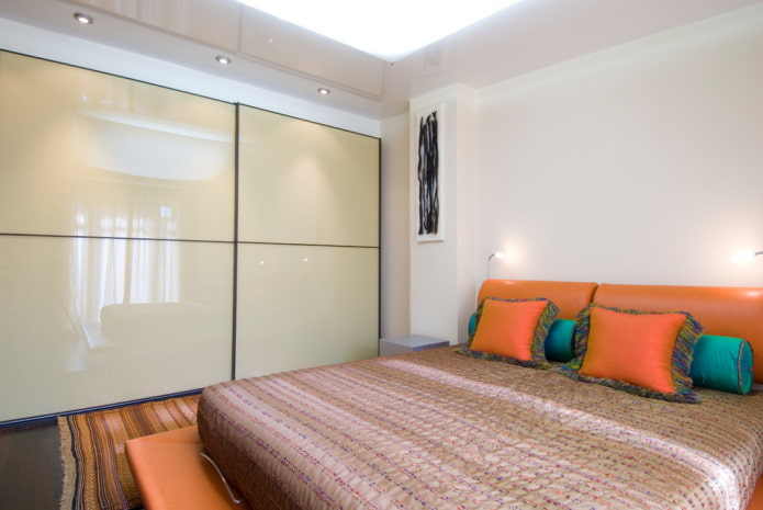 шкаф-купе с глянцевым фасадом в интерьере спальни