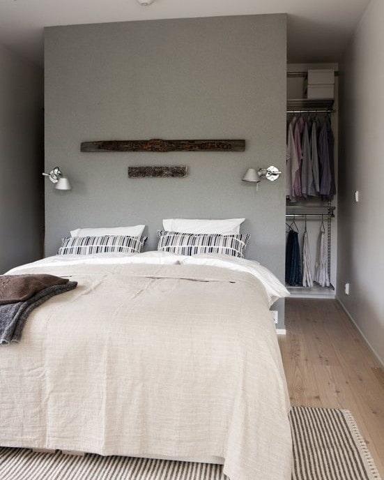 гардеробная за кроватью в интерьере спальни