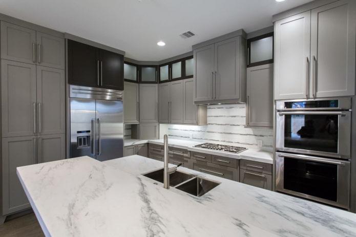кухня со светло-серой мебелью и столешницами из белого камня