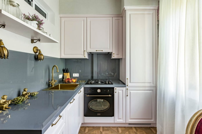 маленькая кухня с белой мебелью, серыми столешницами и фартуком из того же материала