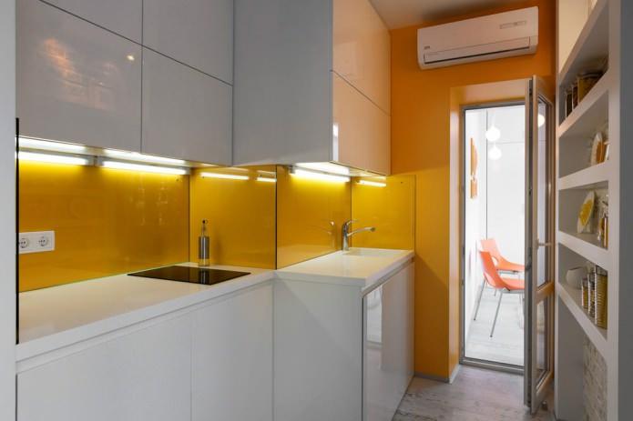 кухня в дизайне квартиры-студии в оранжево-белых тонах